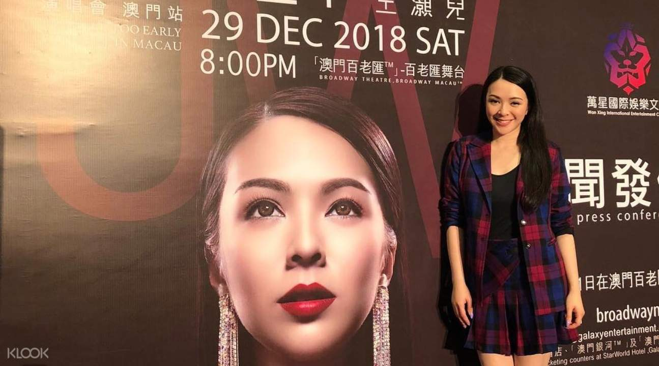 JW standing beside the poster for her tour