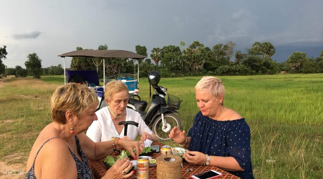Three women enjoy Khmer dish outdoors