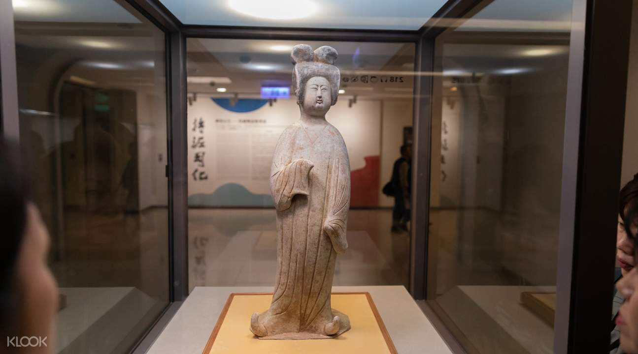 Pottery figure of a standing lady with painted colors on display at the National Palace Museum