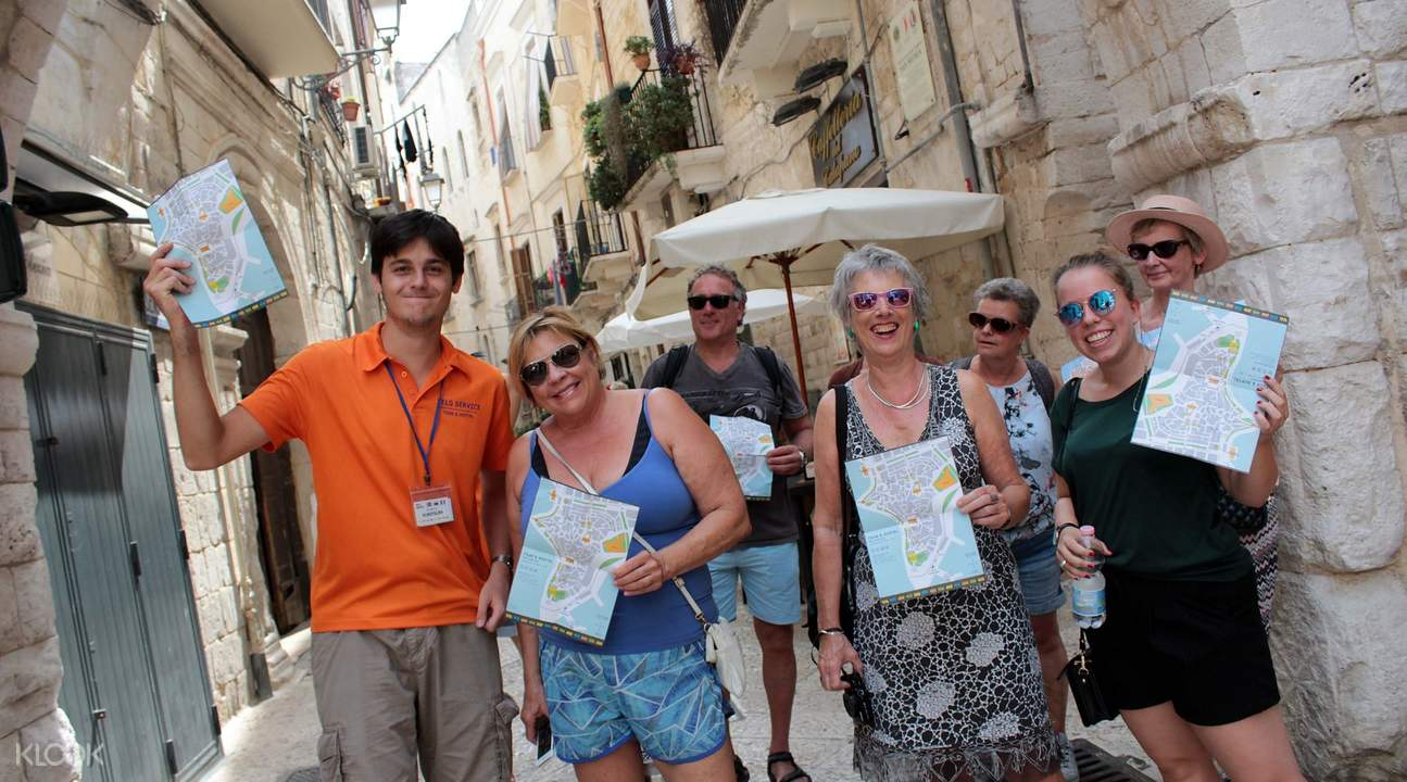tour guide and group in bari holding map