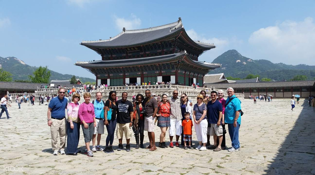tourists taking a picture in front of Gyeongbokgung in seoul, on traditional culture course