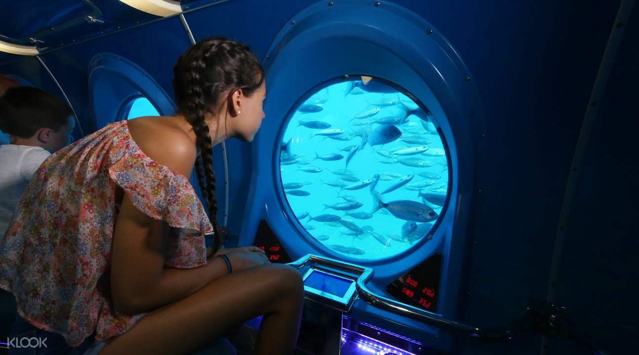 girl looking out of submarine window at fish