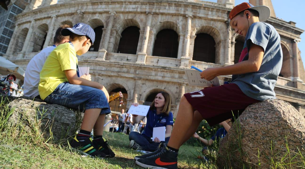kids participating in an educational activity with the tour guide in front of the Colosseum