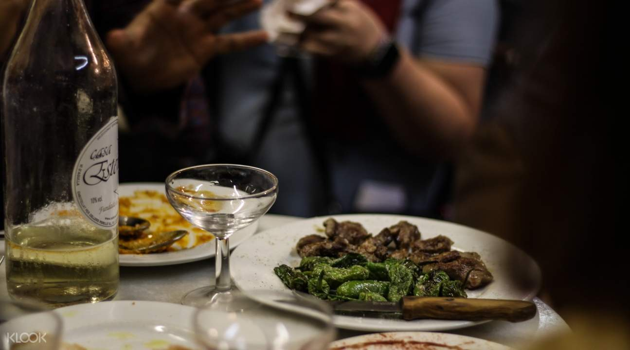 a plate of beef and greens with a bottle of wine to the left