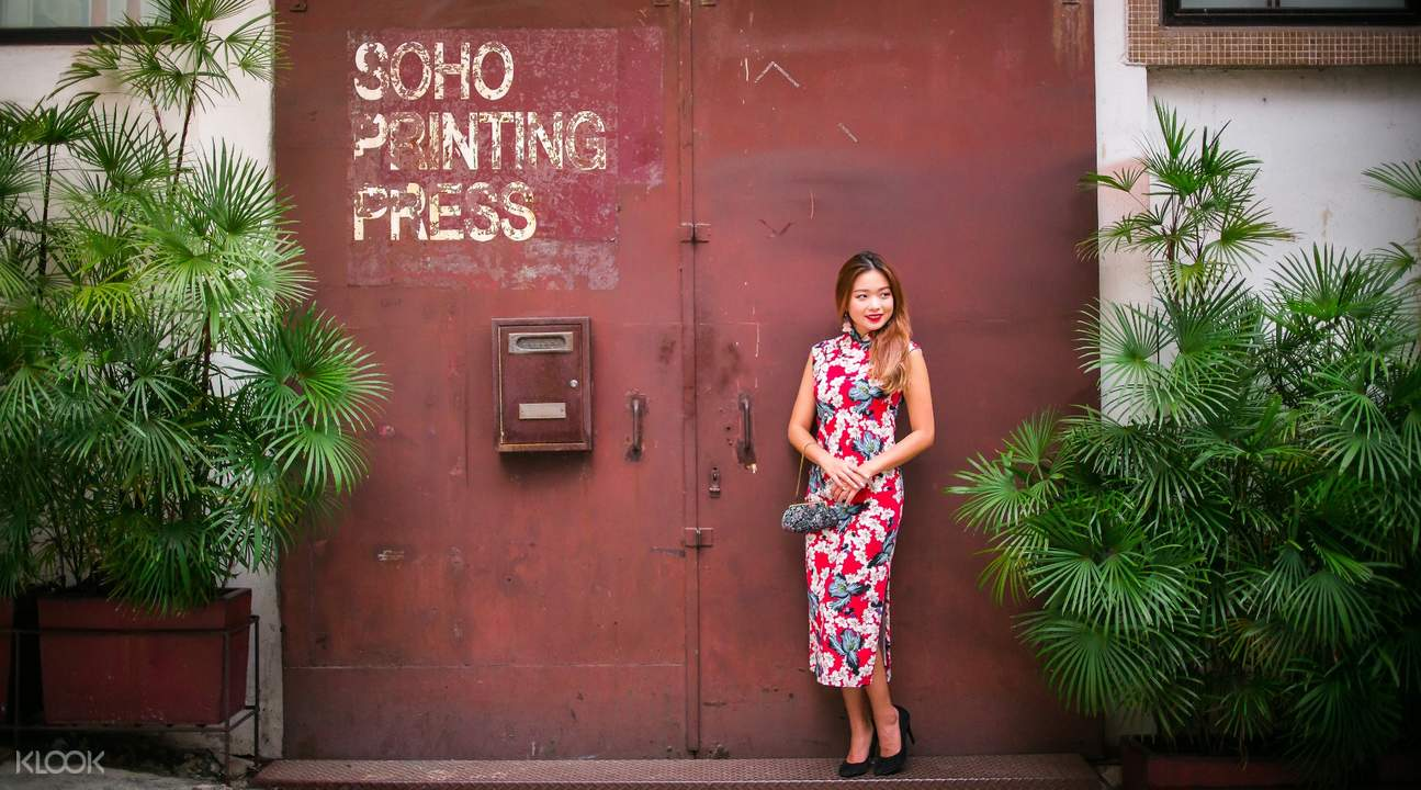 woman wearing qipao costume behind red door