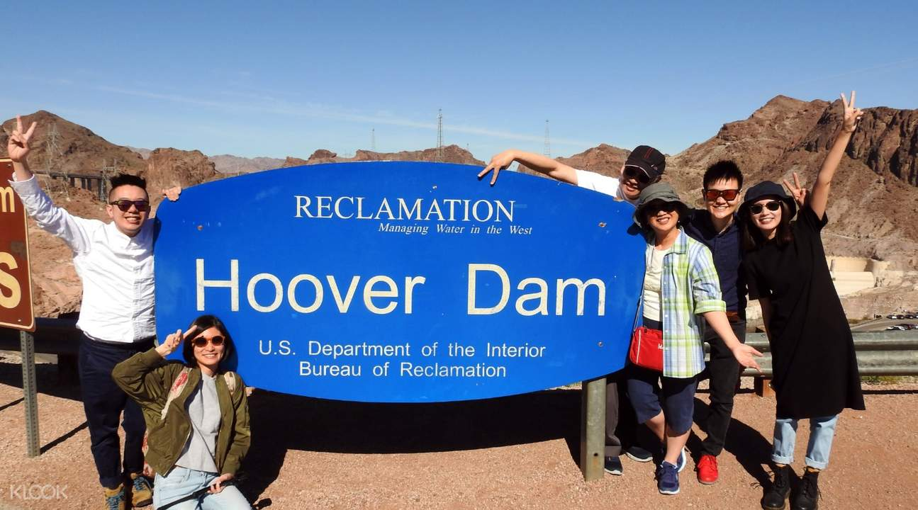 people posting in front of hoover dam sign