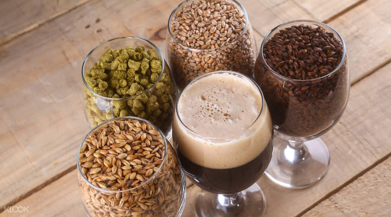 glasses; one of them has beer; all the other glasses are filled to the brim with seeds and beans