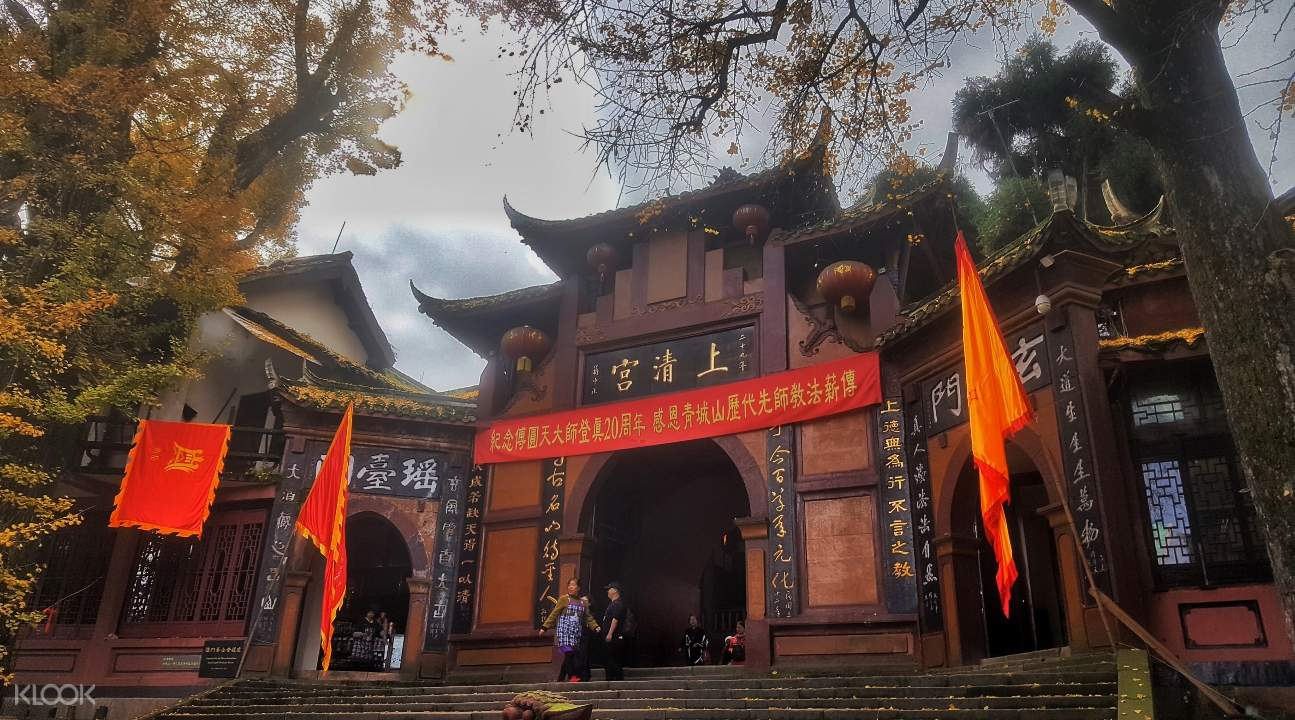 an entrance to a Taoist temple; there are orange banners and flags as well as people by the steps