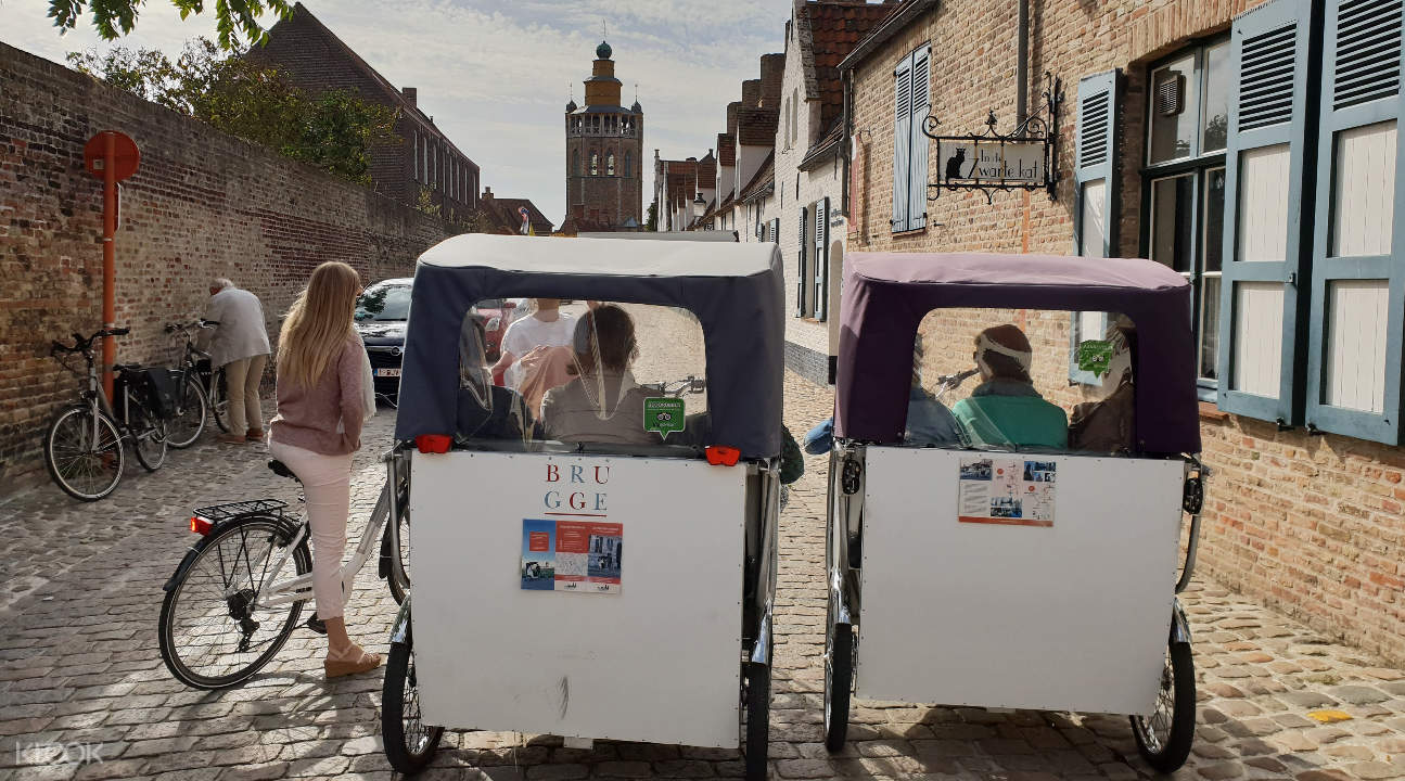 two rickshaws along a cobbled street in Bruges
