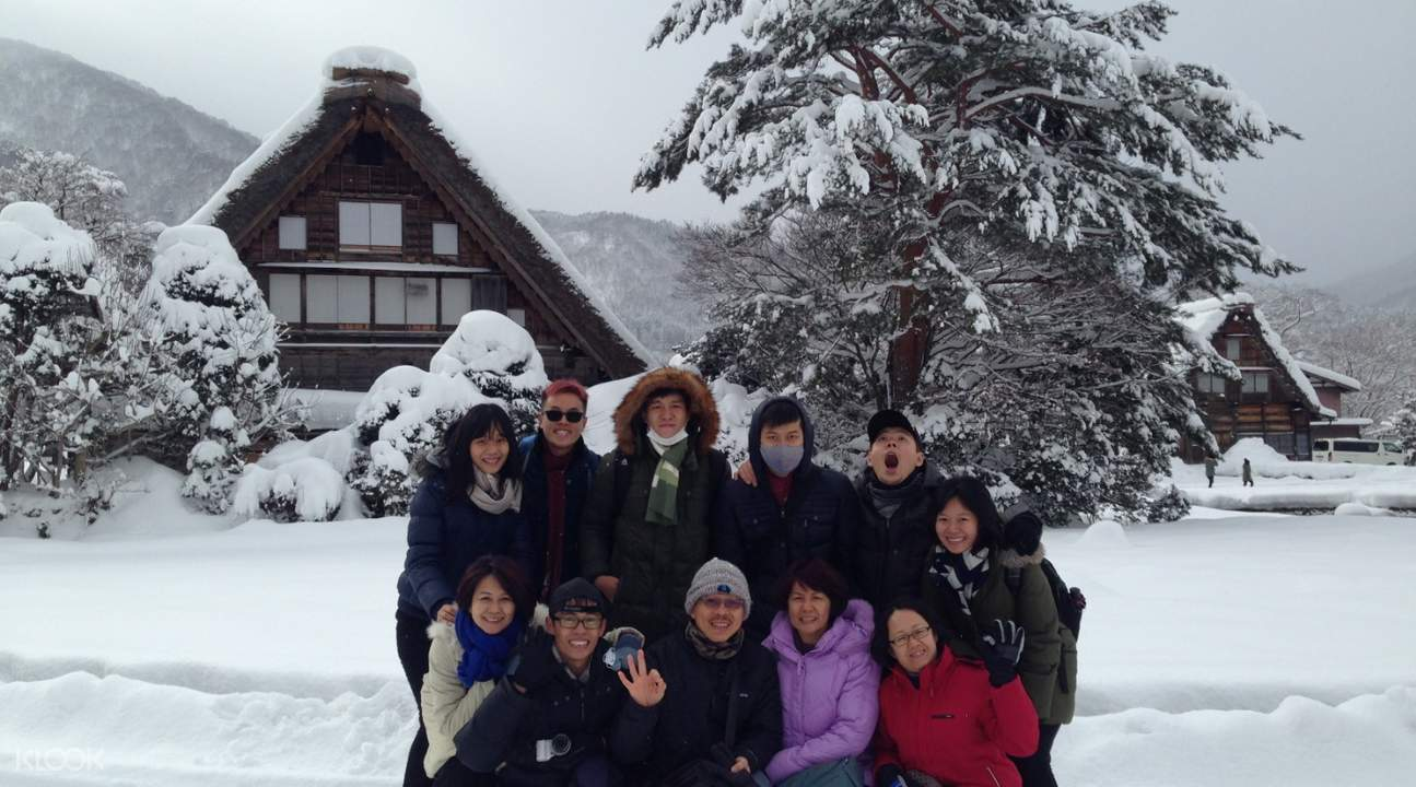 tour group taking pictures with gassho-zukuri farmhouses in Ogimachi Village