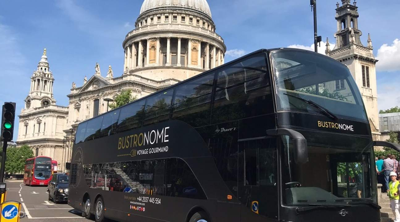 a black Bustronome luxury bus parked in front of a building in London