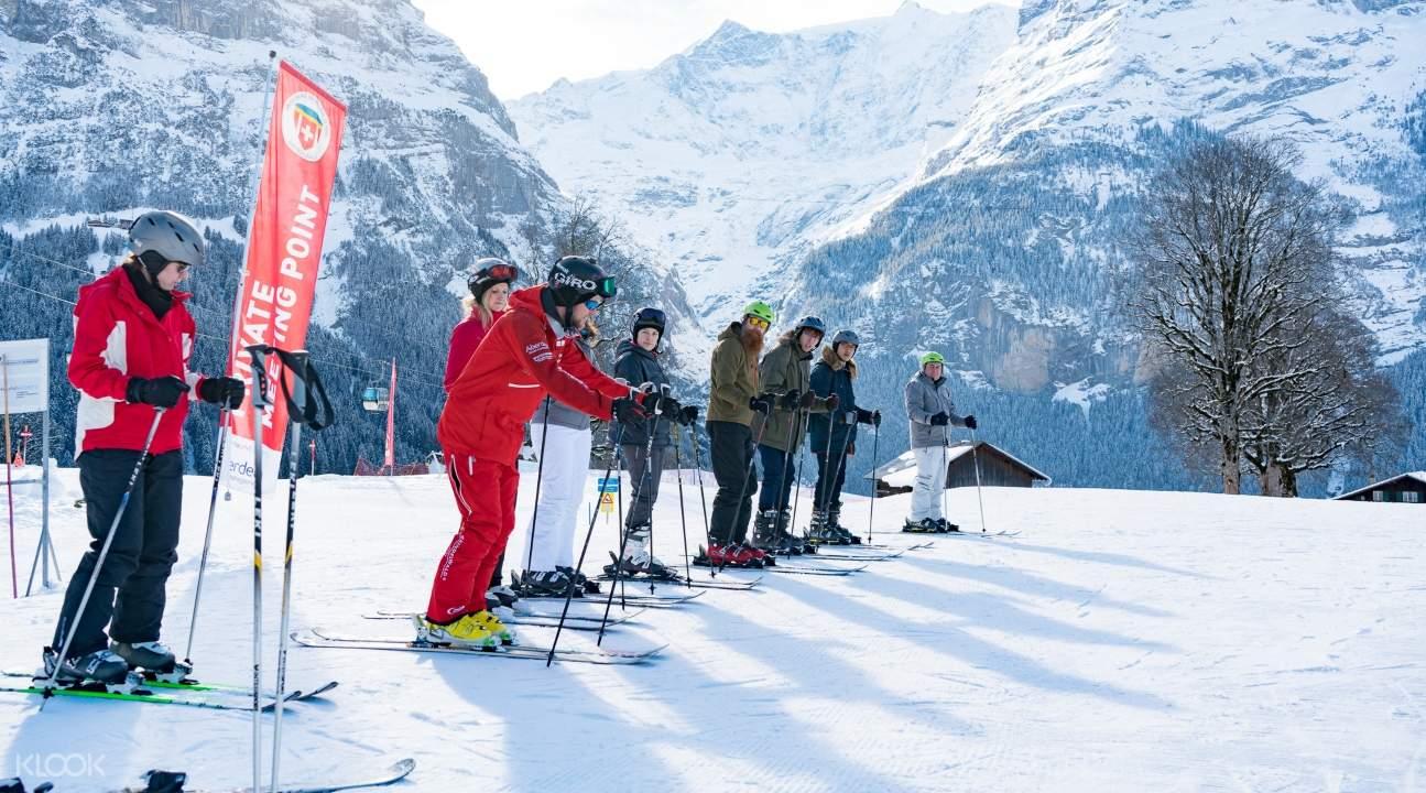 an instructor alongside beginner skiers