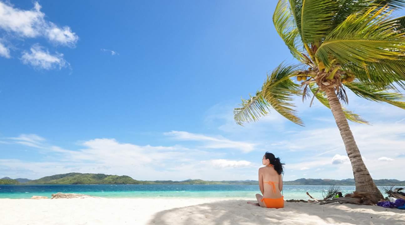 woman sitting under coconut tree in pass island coron