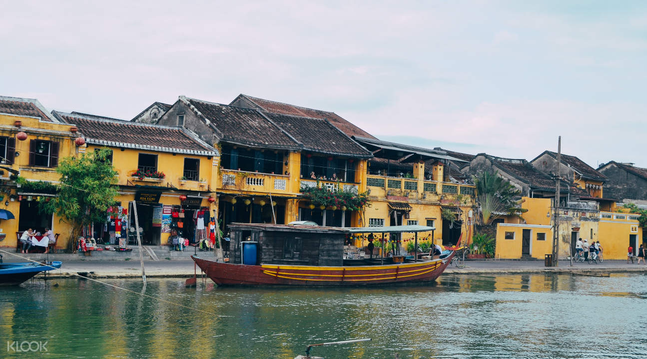 a river in Hoi An with a view of a building and a boat