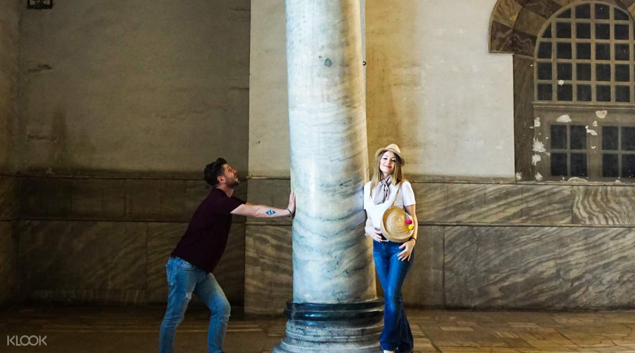man and woman standing next to pillar in hagia sophia