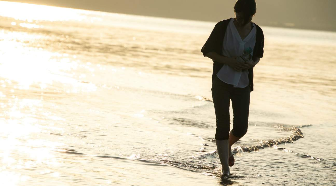 woman walking across the kuroshima venus road sandbars