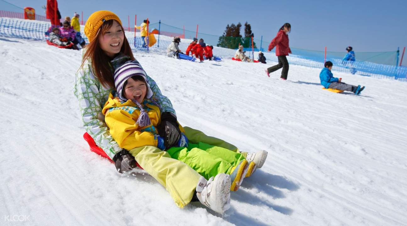 woman and child sledding down slope of Biwako Valley Ski Resort