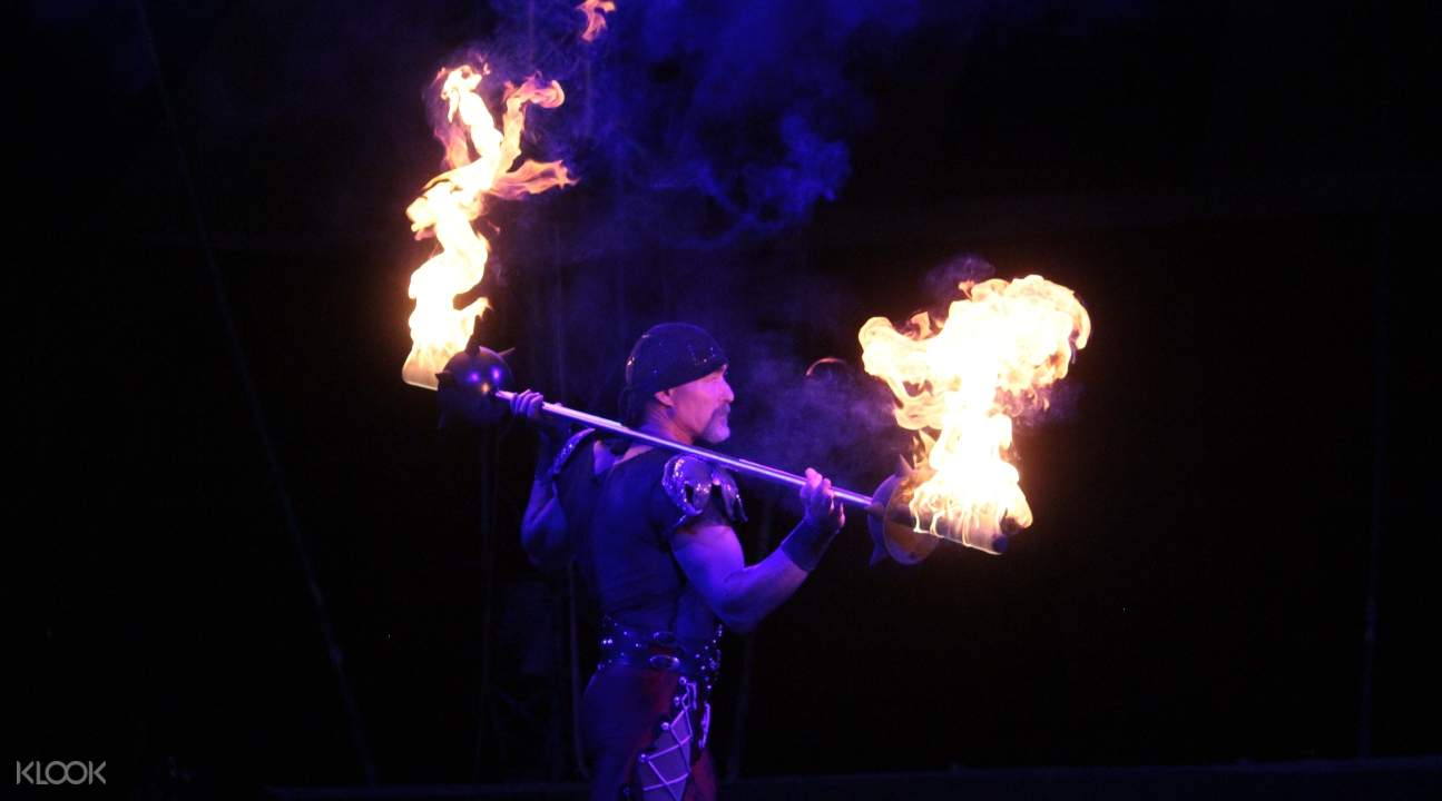 a burly man carrying a pole with fire on both of its ends
