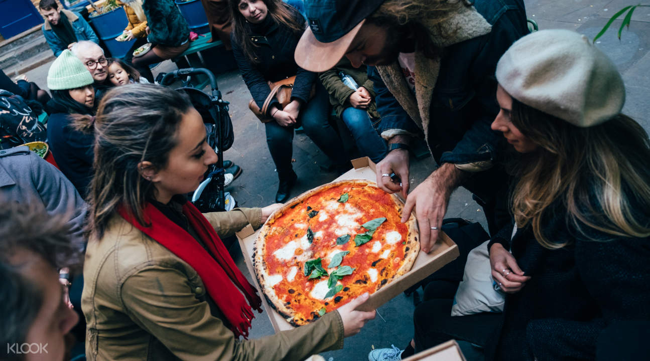 people enjoying a margherita pizza made with prosecco cheese