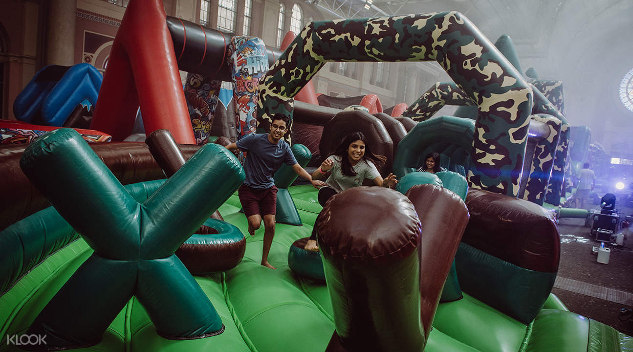 people running through brown and green obstacles; some of the obstacles have the shape of X
