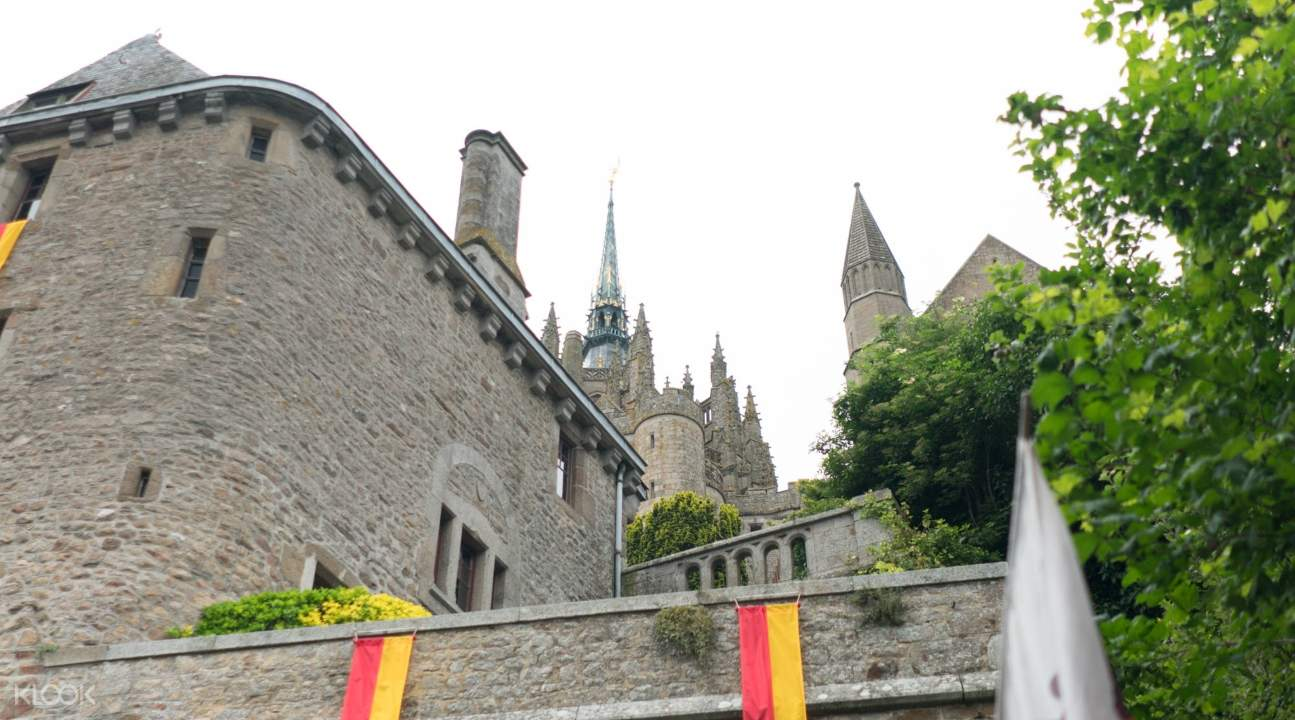 a view of the abbey though slightly blocked by quaint medieval houses; the center spire can be seen