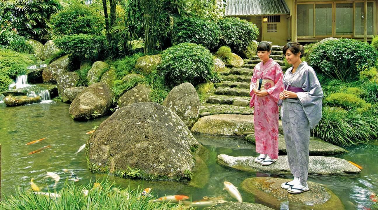 two women in kimonos feeding koi fish at the Japanese Village