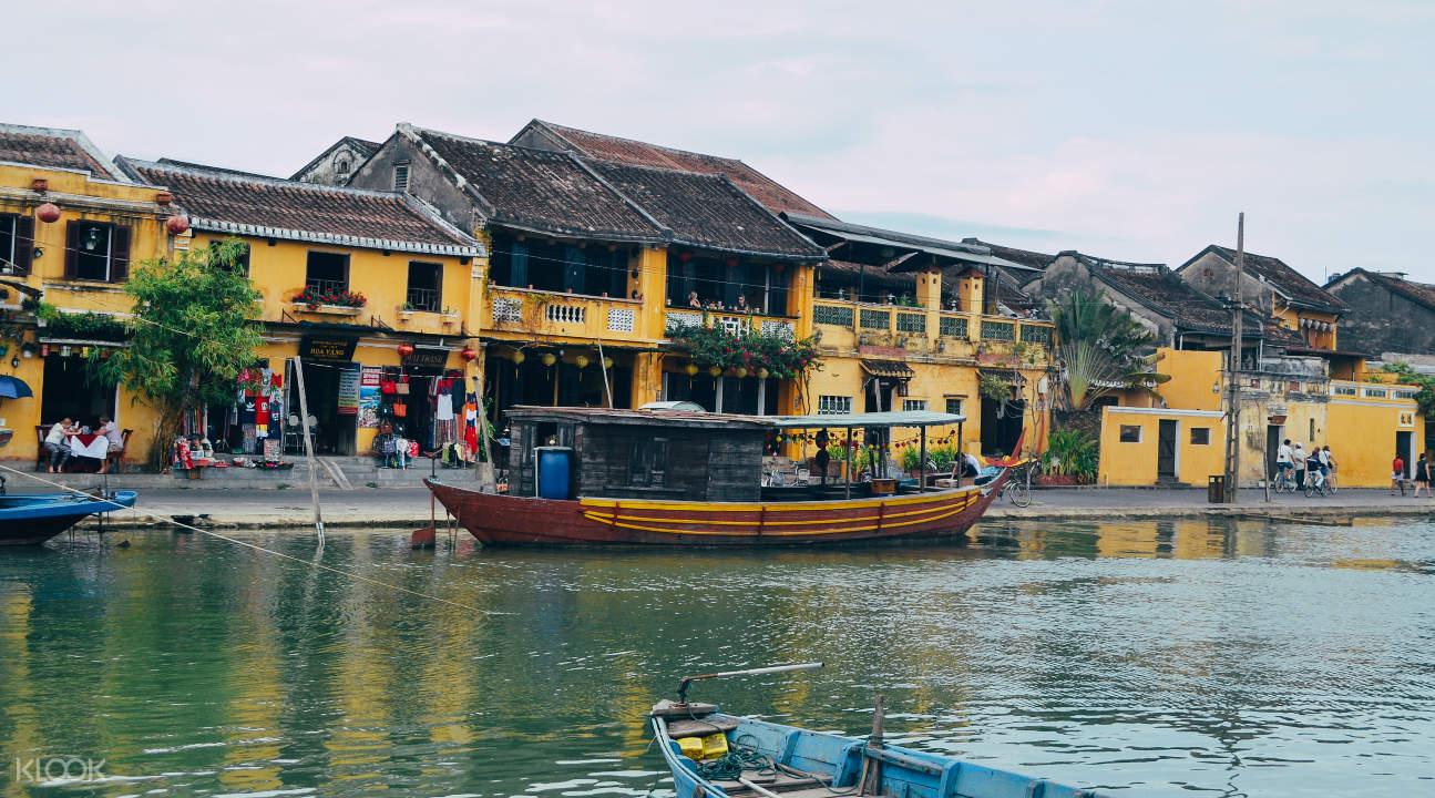 a river in Hoi An with a view of a boat and a building
