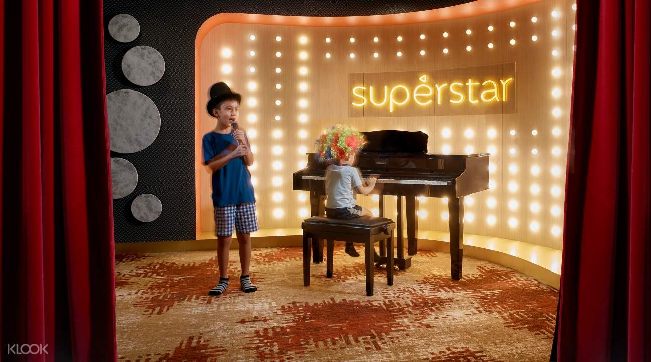 a kid wearing a hat is singing and a kid with a colorful afro is playing piano