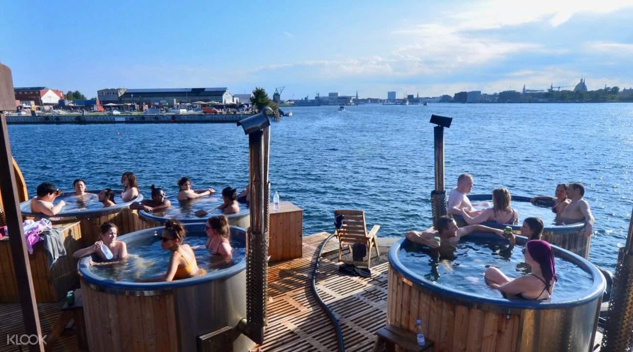 People in tubs at the edge of a harbour in CopenHot, Copenhagen
