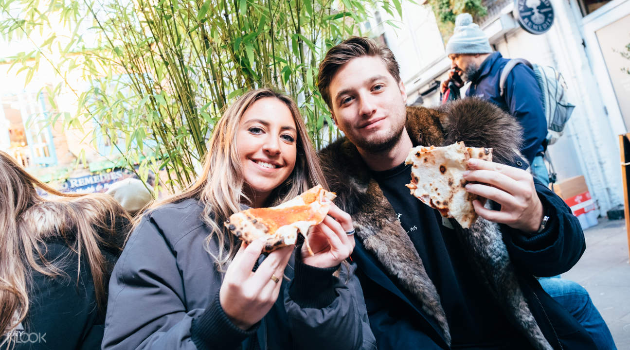 a couple enjoying a cheesy delight somewhere in London