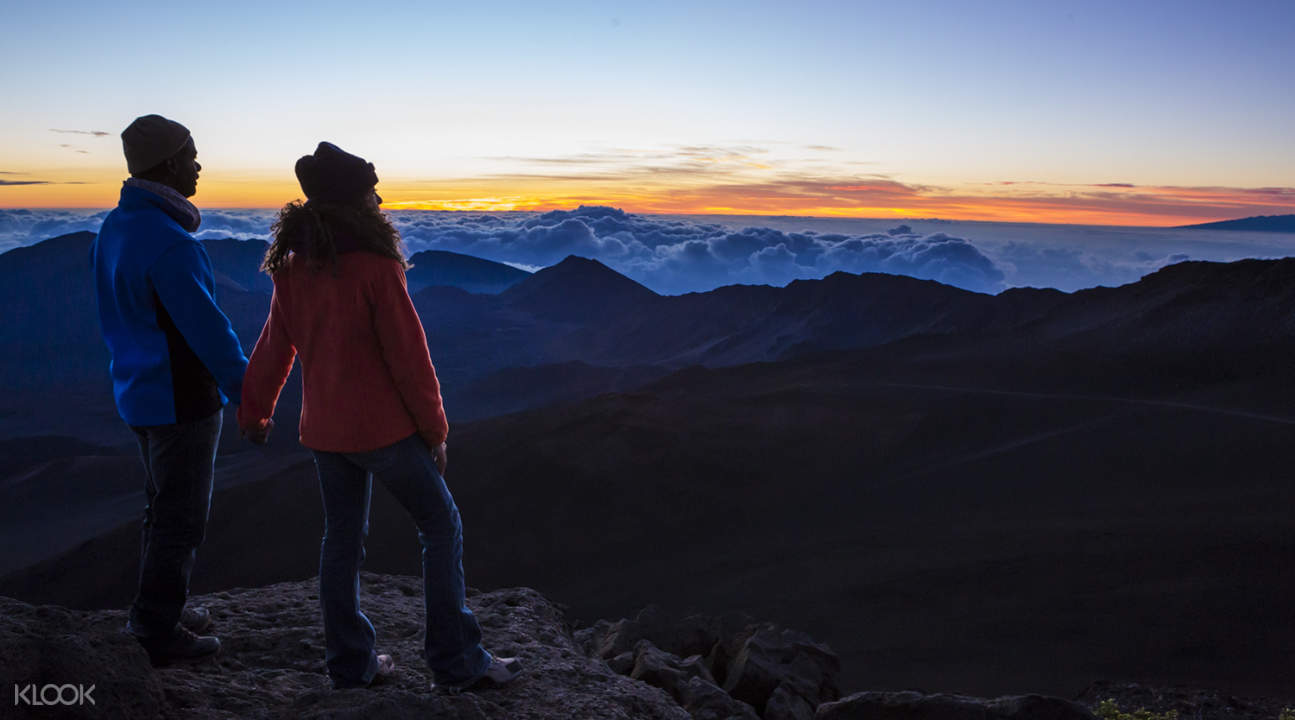 a couple watching the sunrise at Haleakala