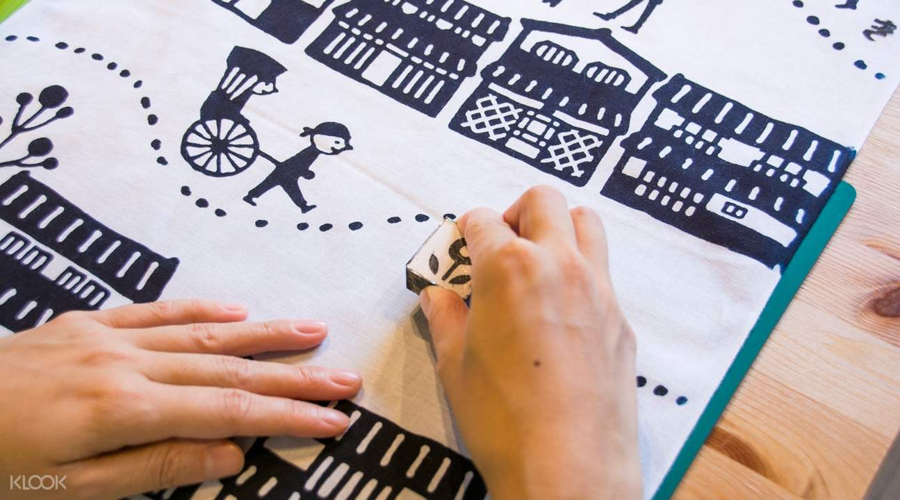 hands on a cotton towel; one hand is using a stamp to make designs