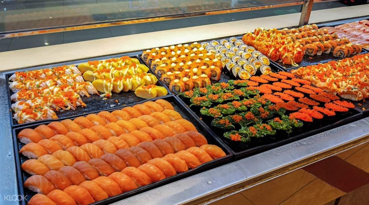 Variety of sushi and rolls, featuring salmon, crab sticks, or shrimp at Sukishi Buffet in Bangkok
