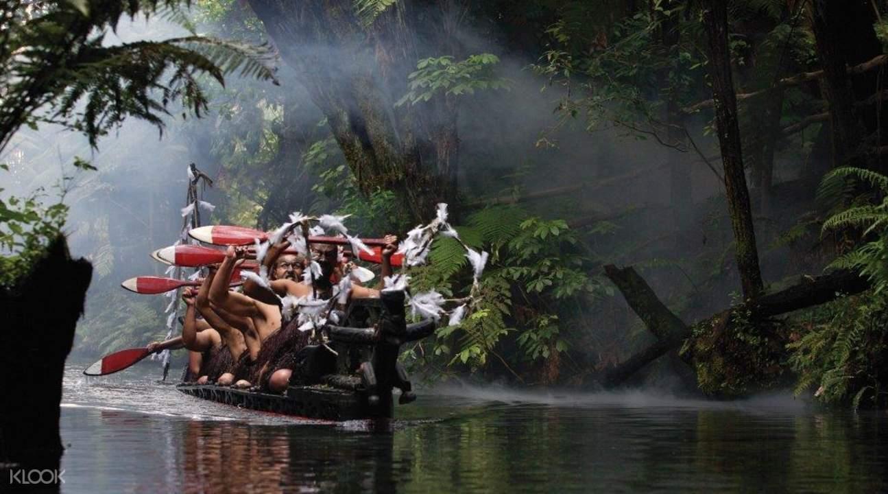 毛利人搭乘著傳統的船只Waka在熱帶雨林的河流上前進