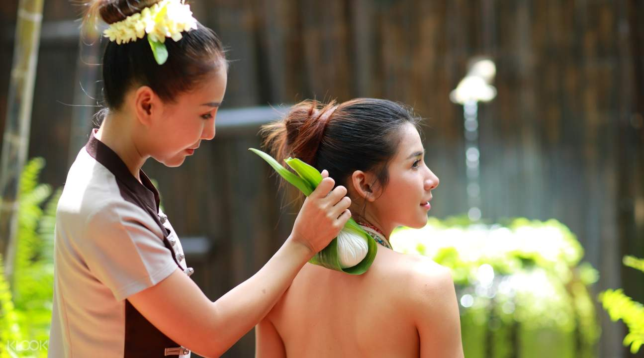 masseuse rubbing herb on woman