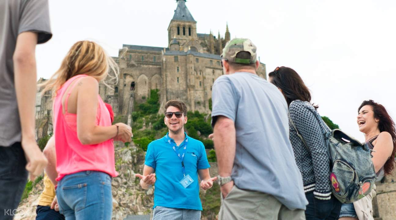 a tour guide talking to tourists about Mont-Saint-Michel