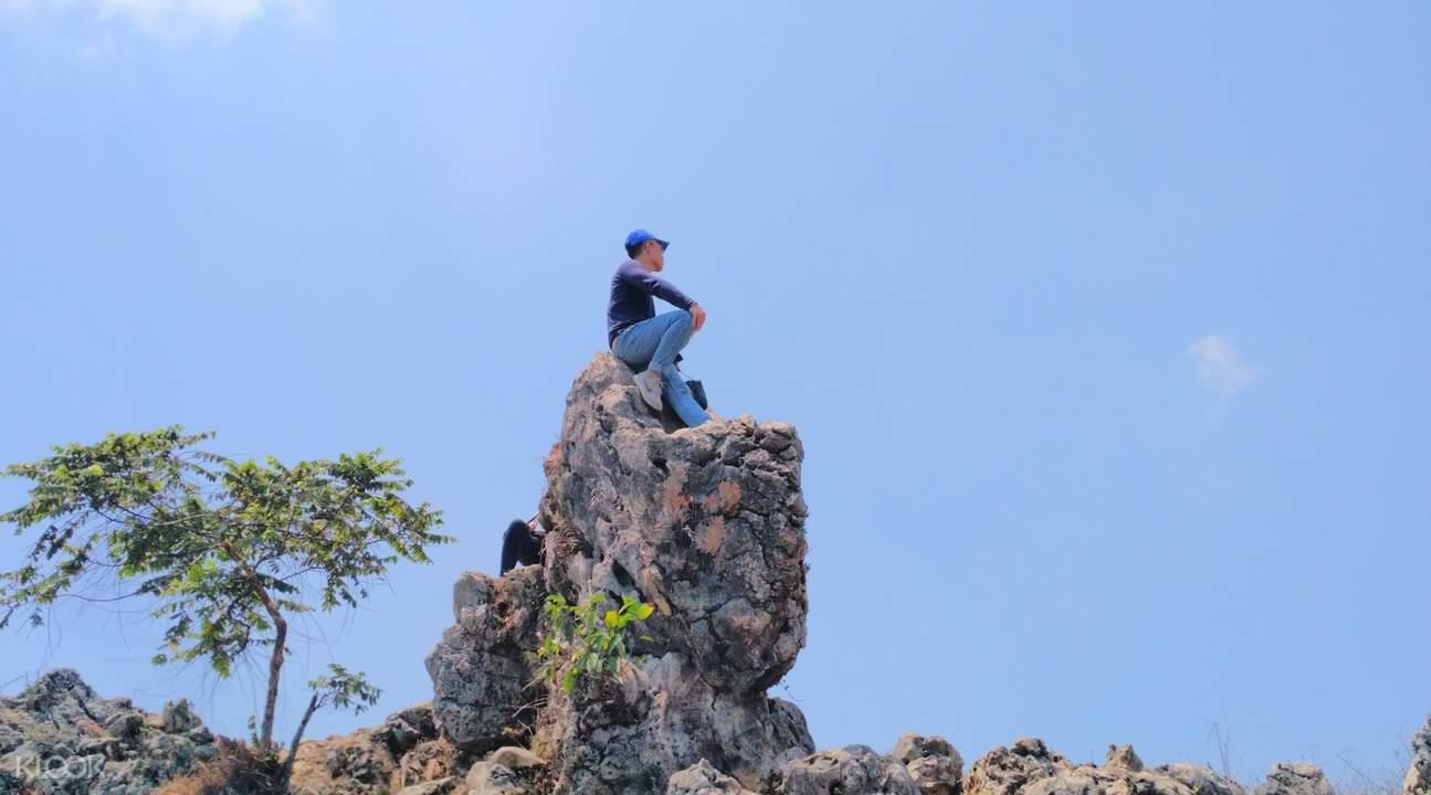 man sitting on top of rock