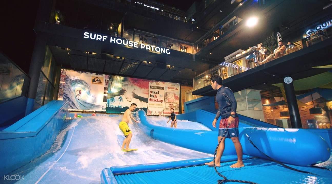 people riding waves at kata beach surf house