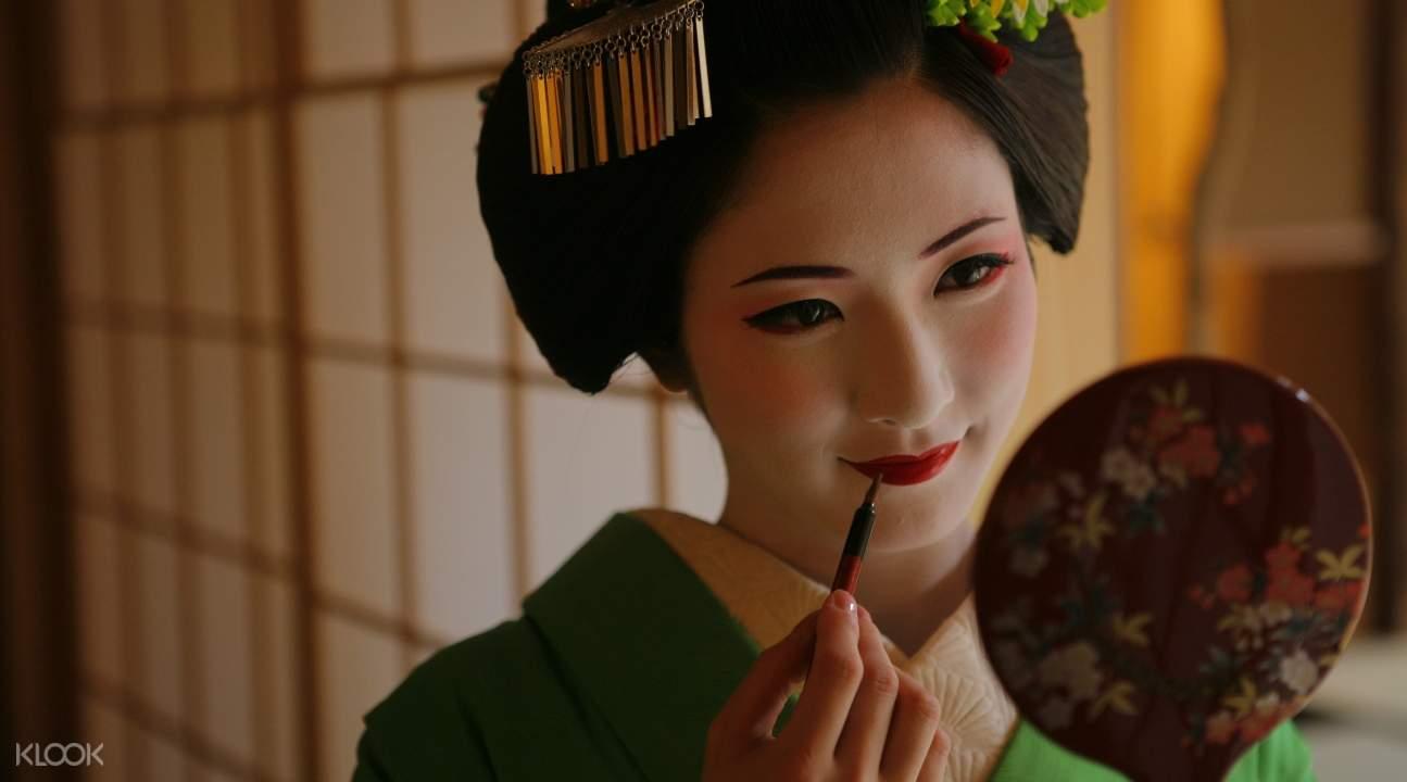 a maiko putting makeup on herself