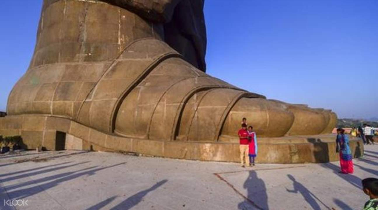 tourists taking photos next to the foot of the statue of unity