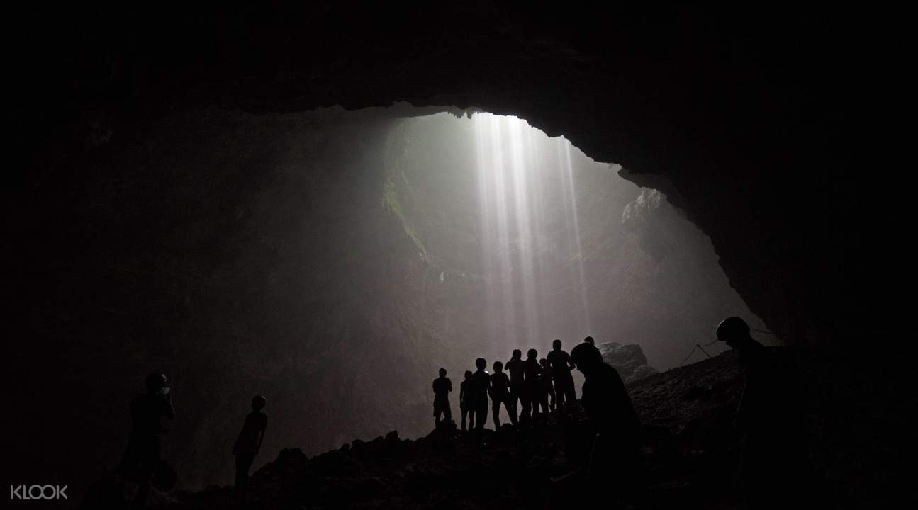 beautiful ray of light in jomblang cave with group tourists
