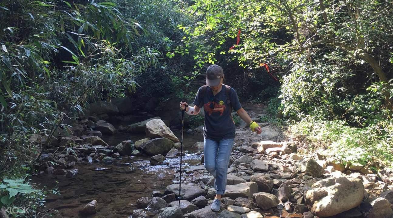 woman walking with stick on rocks