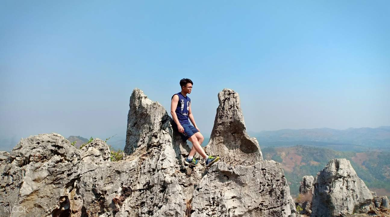 man posing on top of rock formation