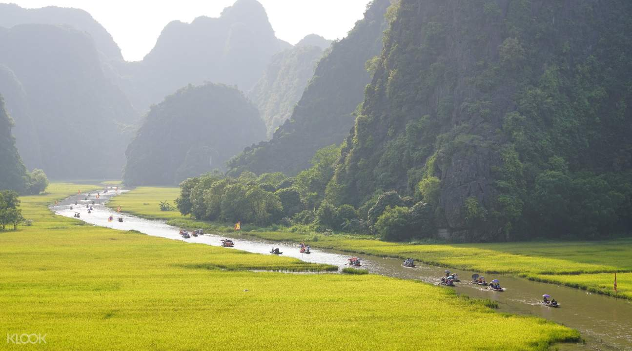 sampan boats sailing in between fields and mountains