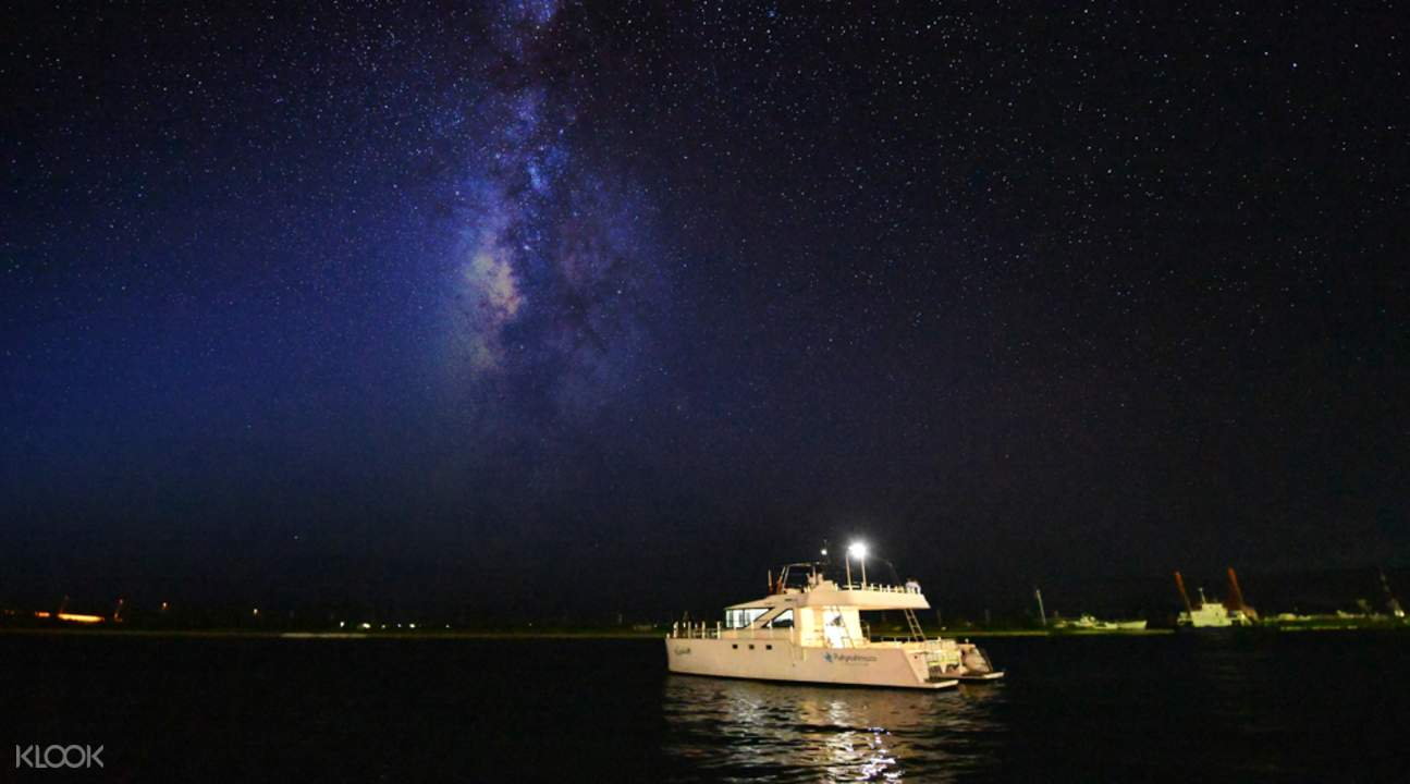 boat sailing by ishigaki island at night