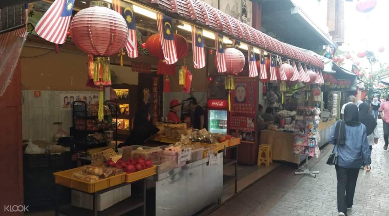 People walking next to food stalls in Ipoh