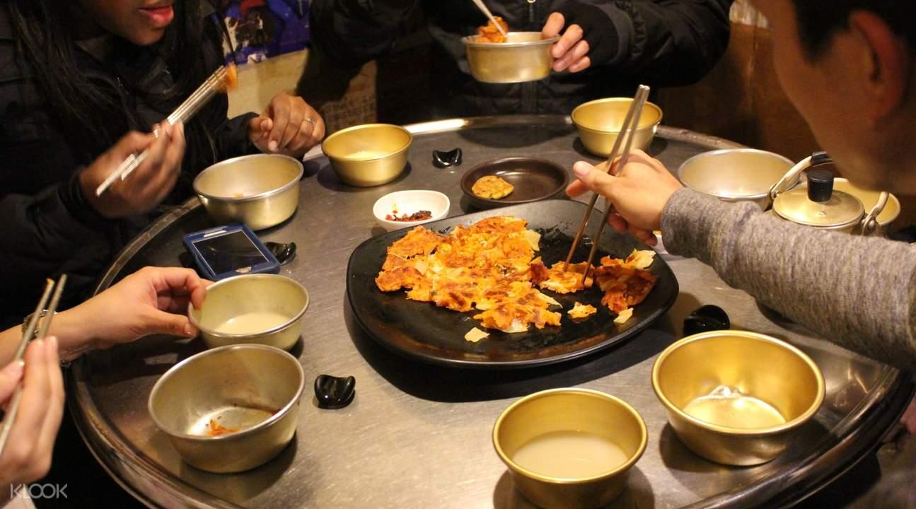 chopsticks picking up kimchi pancake