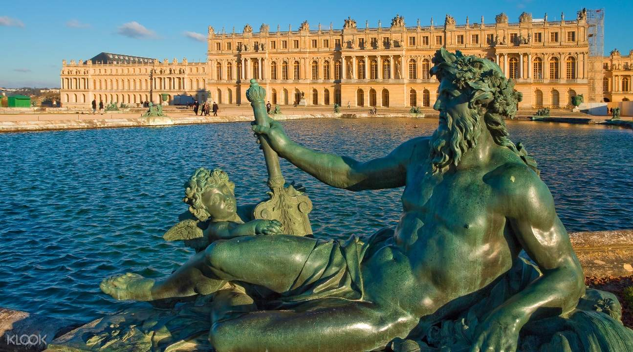a view of Versailles from a river; a statue is blocking a small section of the castle