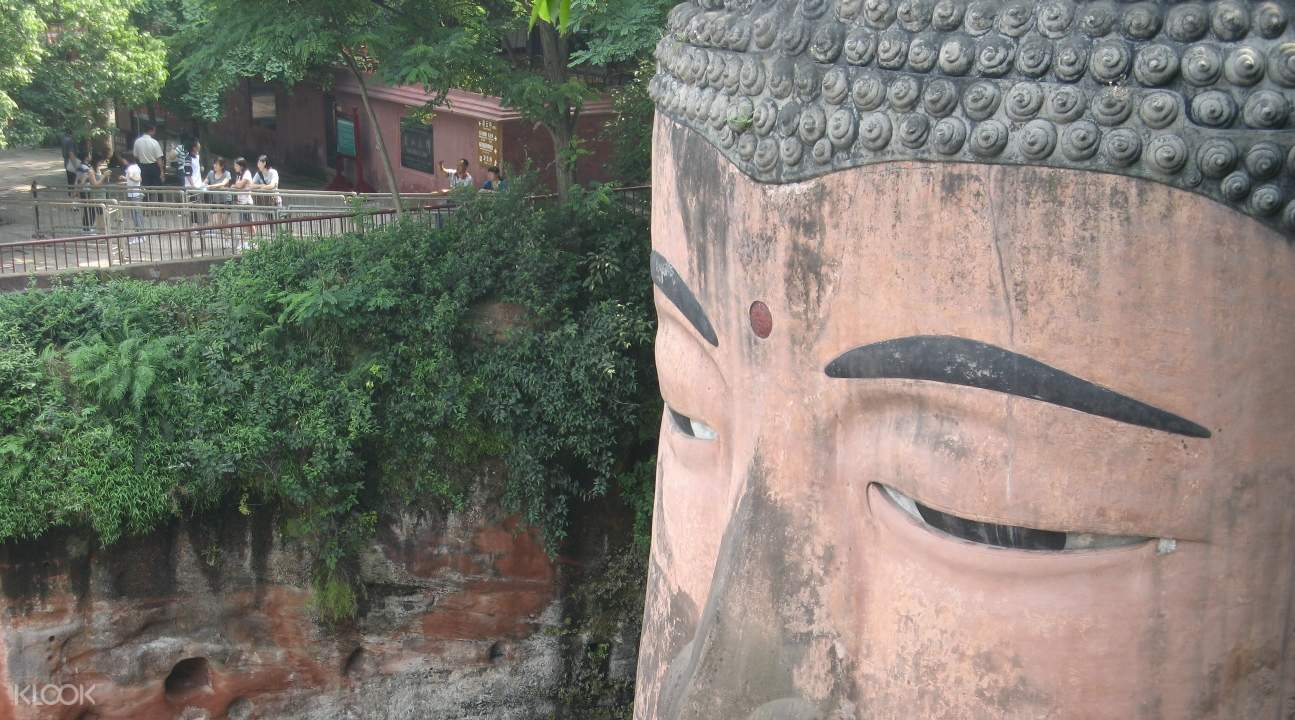 a close-up of the Giant Buddha's face with people near it