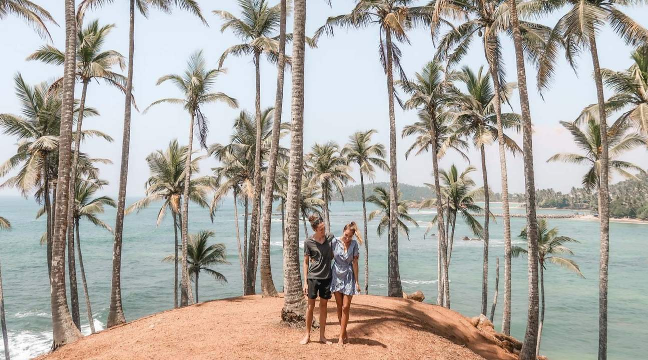 man and woman standing in coconut tree hill